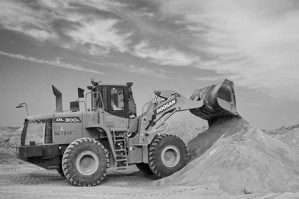 Earth mover lifting sand